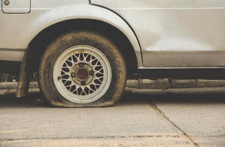 Close up of flat tire on silver vehicle