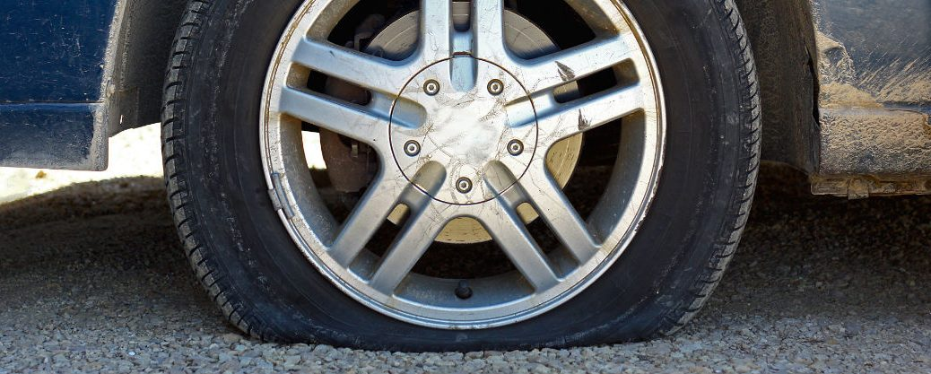 Close up of a flat tire on a gravel road