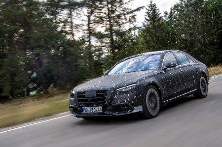 MB S-Class exterior front fascia driver side on blurred road with pine trees