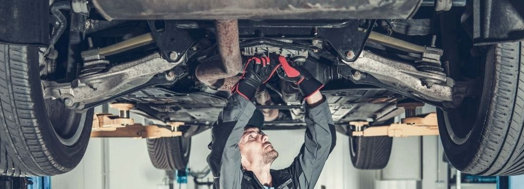 mechanic changing oil with car above