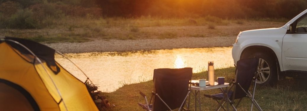 close up of tent and camping chairs by water with white SUV