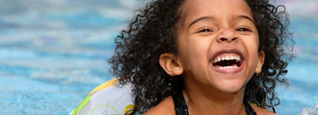 Child playing in water smiling