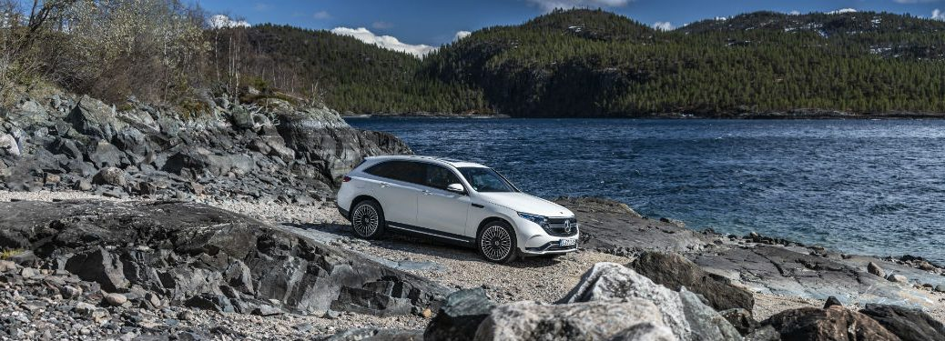 2020 MB EQC exterior front fascia passenger side rocky road next to hill and water