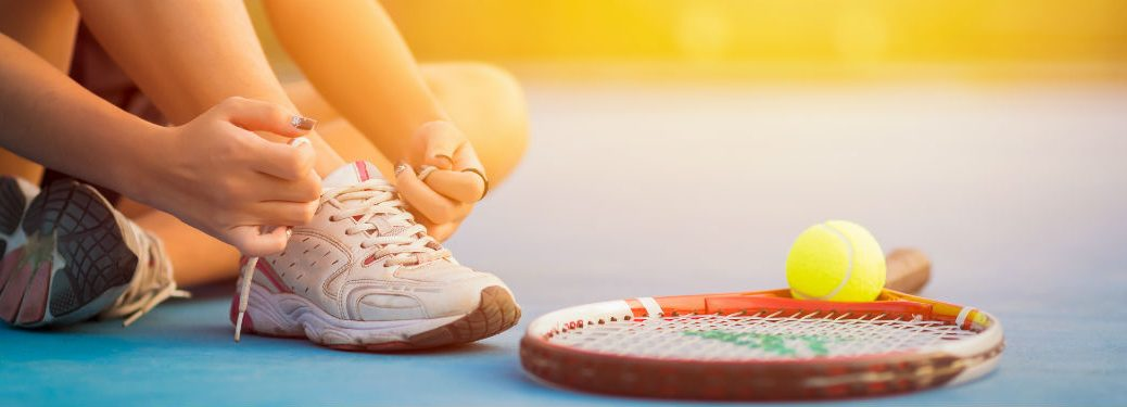 Tennis player lacing up shoe with racket and tennis ball in front of her
