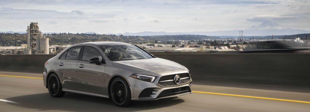 2019 MB A-Class exterior front fascia and passenger side on highway with city in background