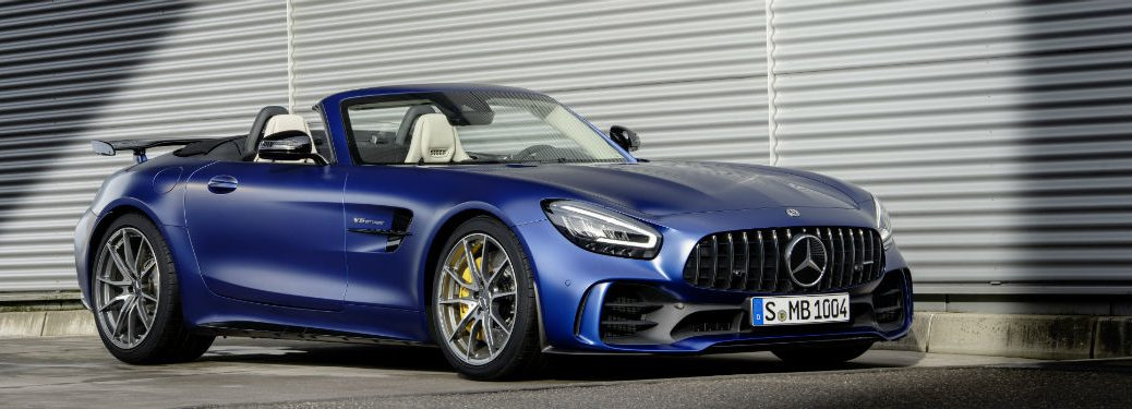 2020 MB AMG® GT R Roadster exterior front fascia and passenger side hood down next to garage door