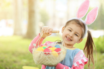 Little girl with bunny ears and Easter egg basket outdoors