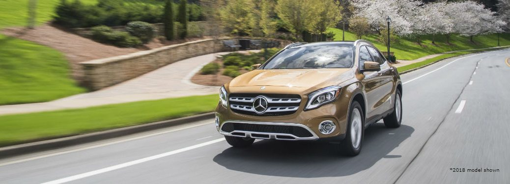 2018 MB GLA exterior front fascia and drivers side going fast on town road with sidewalk and trees