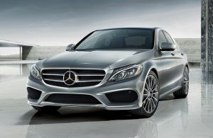 2019 MB C-Class Sedan exterior front fascia and driver side on tiled lot with dark gray sky