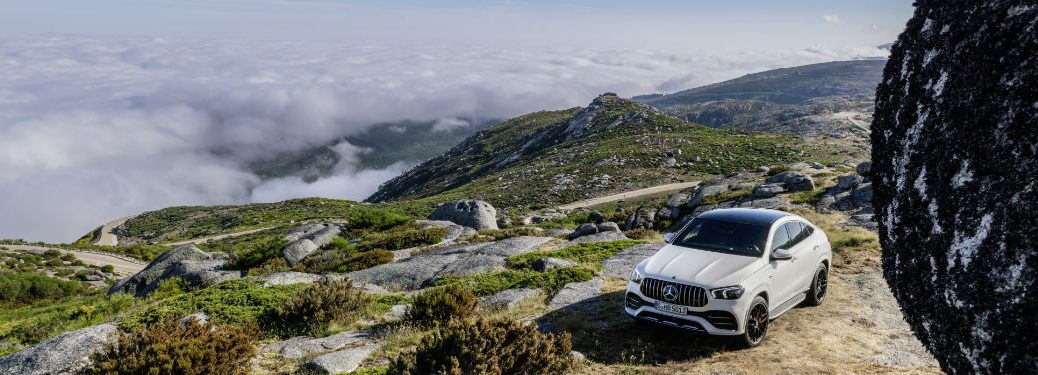 2021 MB GLE Coupe exterior front fascia and driver side on mountain overlooking clouds