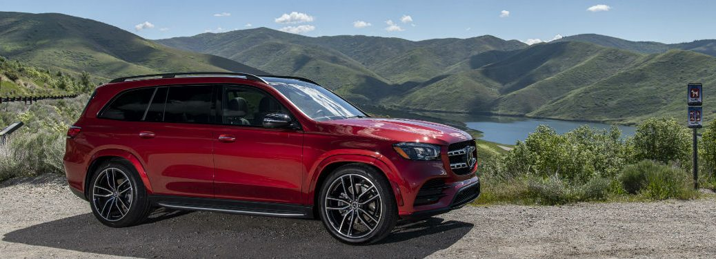 2020 MB GLS exterior front fascia and passenger side overlooking mountains and lake