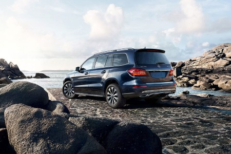 Rear driver angle of a blue 2019 Mercedes-Benz GLS parked by the ocean