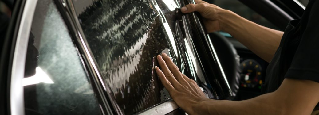 window tint being installed on passenger window of car
