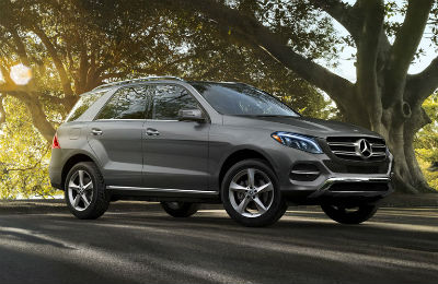 2019 MB GLE exterior front fascia and passenger side in front of tree with sunlight streaming