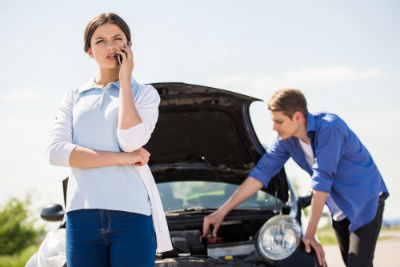 woman calling for help while man looks under hood of car