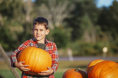 Boy holding large pumpkin next to pumpkin stack