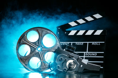 Film reel camera and clapperboard blue glowing background