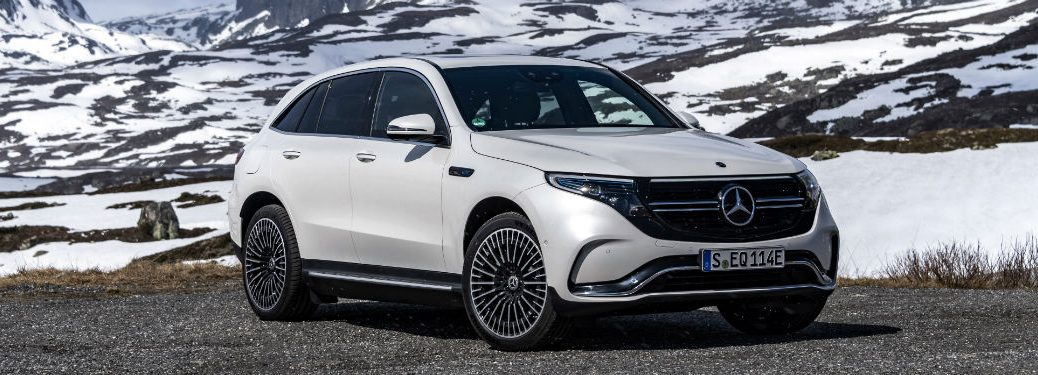 2020 MB EQC exterior front fascia and passenger side in front of snowy mountains