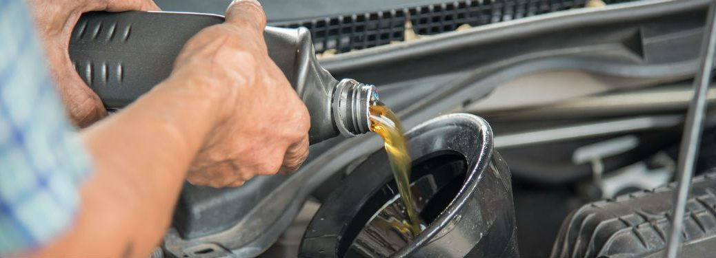 man pouring oil into funnel in car engine