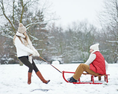 Woman pulling man on sled in snow