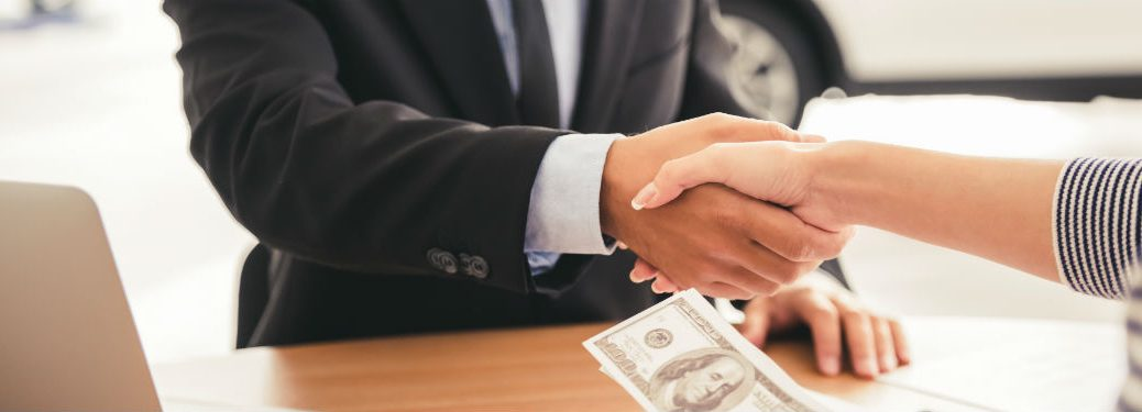 woman shaking salesman hand over paperwork with cash