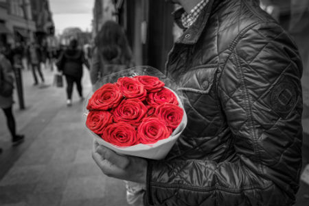 Gray-scale photo of person on city street with vibrant bouquet of red roses