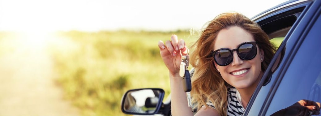 Woman leaning out of car window holding up key on sunny day