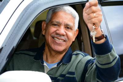 Senior man holding up car key while leaning out of car window