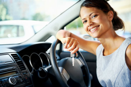 Woman smiling and leaning against steering wheel in car