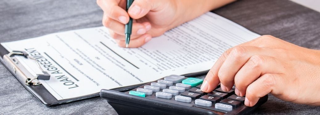 person signing paperwork with calculator