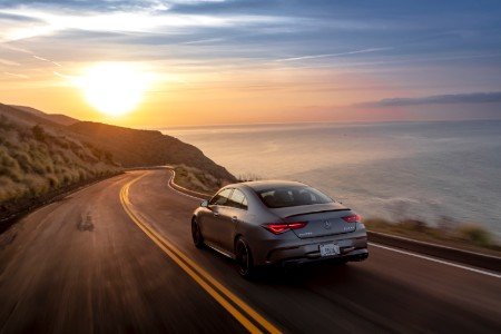 2020 MB CLA exterior rear fascia driver side on highway next to ocean with sun