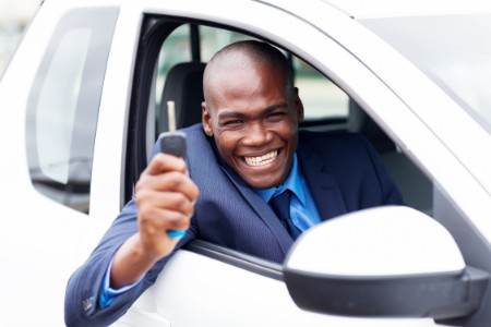 Smiling man leaning out of car window holding up key