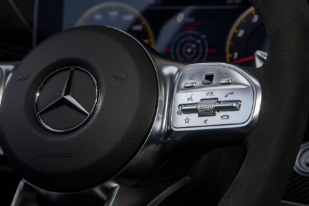 Close up of Mercedes-Benz logo on steering wheel