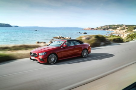 2021 MB E-Class Cabriolet exterior front fascia driver side on blurred highway in front of ocean