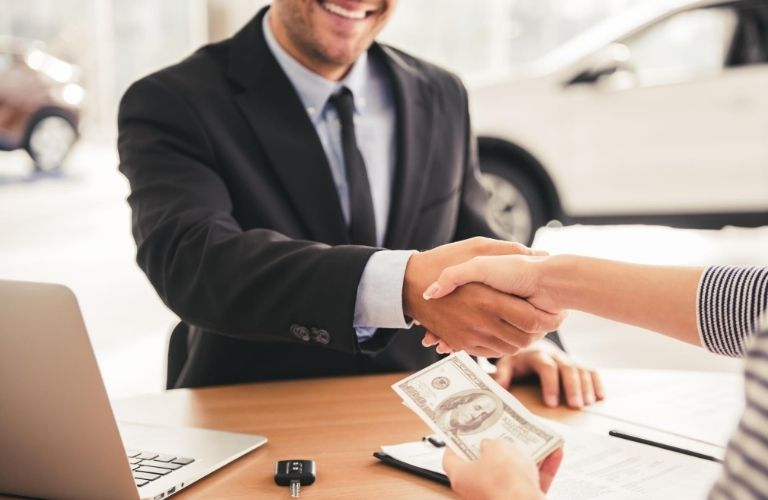 Salesman shaking hands with shopper over table