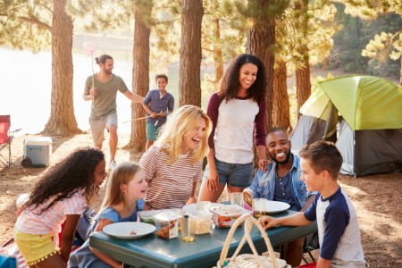 Family at picnic table in campground in woods