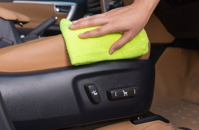 Person wiping down center console of car with yellow cloth