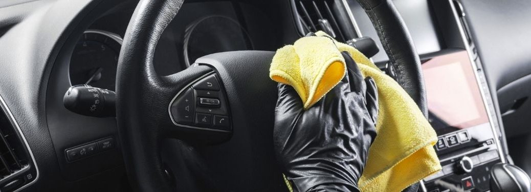 Person wiping down steering wheel with yellow cloth