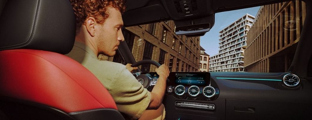 Back seat view of a man driving a Mercedes-Benz GLA SUV while looking at its dashboard