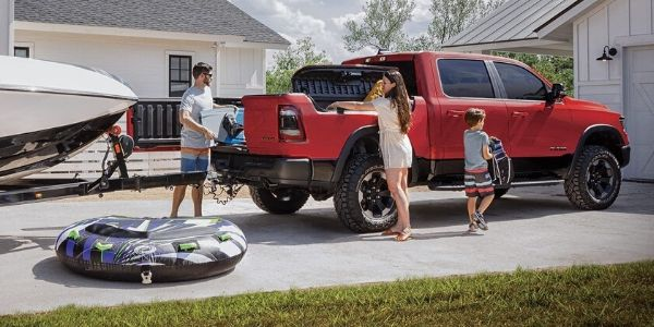 Family Loading Cargo in Red 2020 Ram 1500 Connected to a Boat