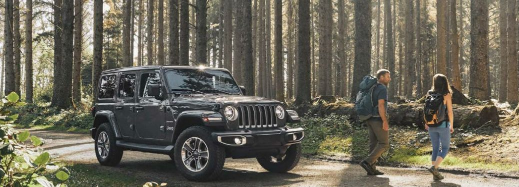 2020 Jeep Wrangler grey exterior front fascia passenger side couple hiking past front end