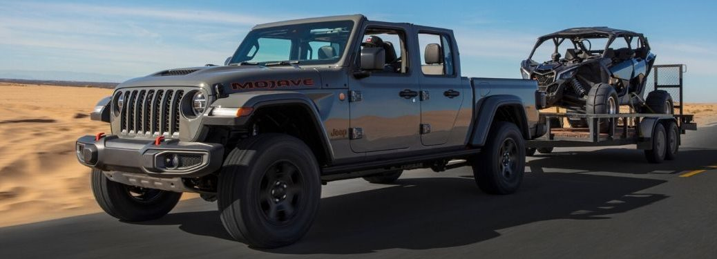 Gray 2020 Jeep Gladiator on a Desert Highway Towing a Trailer with a UTV