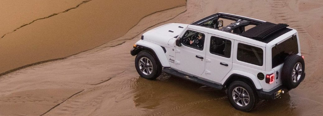 white jeep wrangler unlimited on a beach