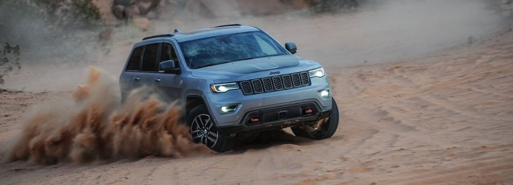 Gray Jeep Grand Cherokee Kicking Up Sand in a Desert