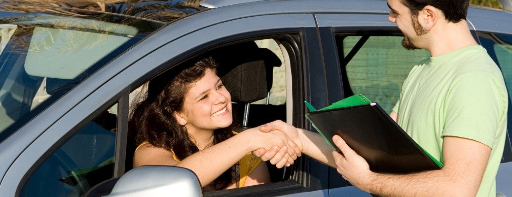 Man giving keys to girl in car