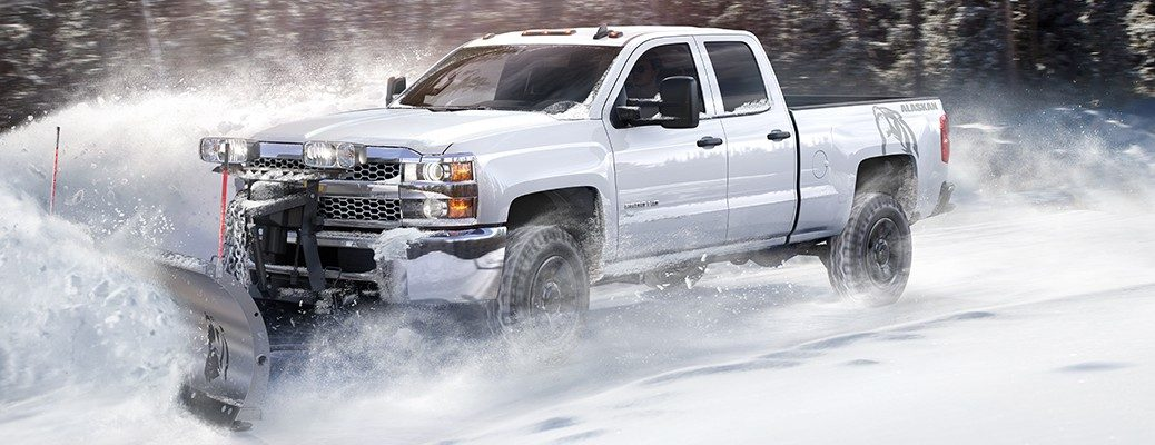 White 2019 Chevrolet Silverado driving on and plowing snowy road