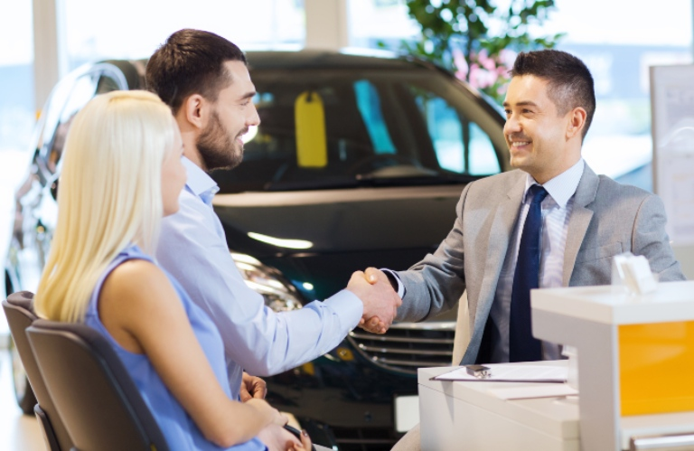 husband and wife buying new car and two men shaking hands