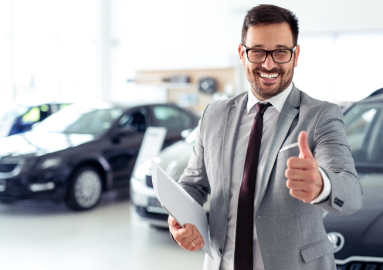 Happy businessman with cars in background