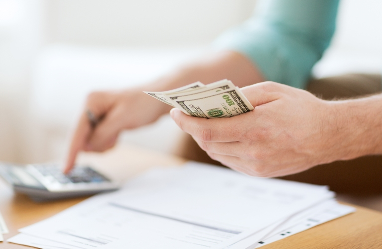 Person Holding Money and Calculating