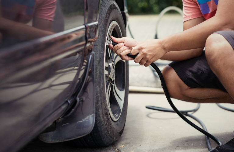 man Filling Tire with Air